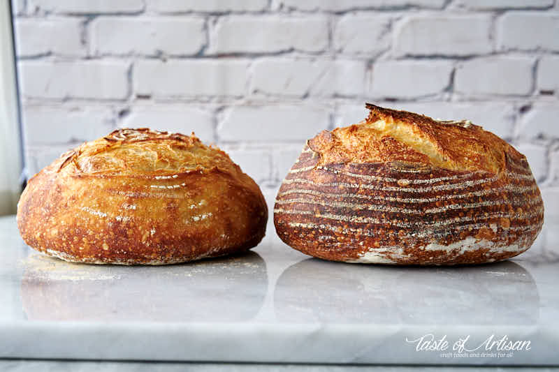 Two loaves of bread side by side on a marble table.