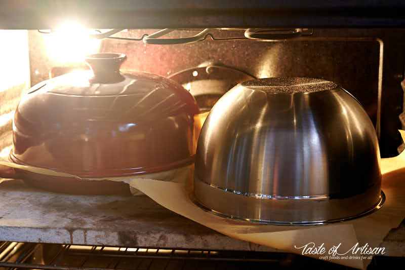 Two loaves in oven, one in a cloche, one under stainless bowl.