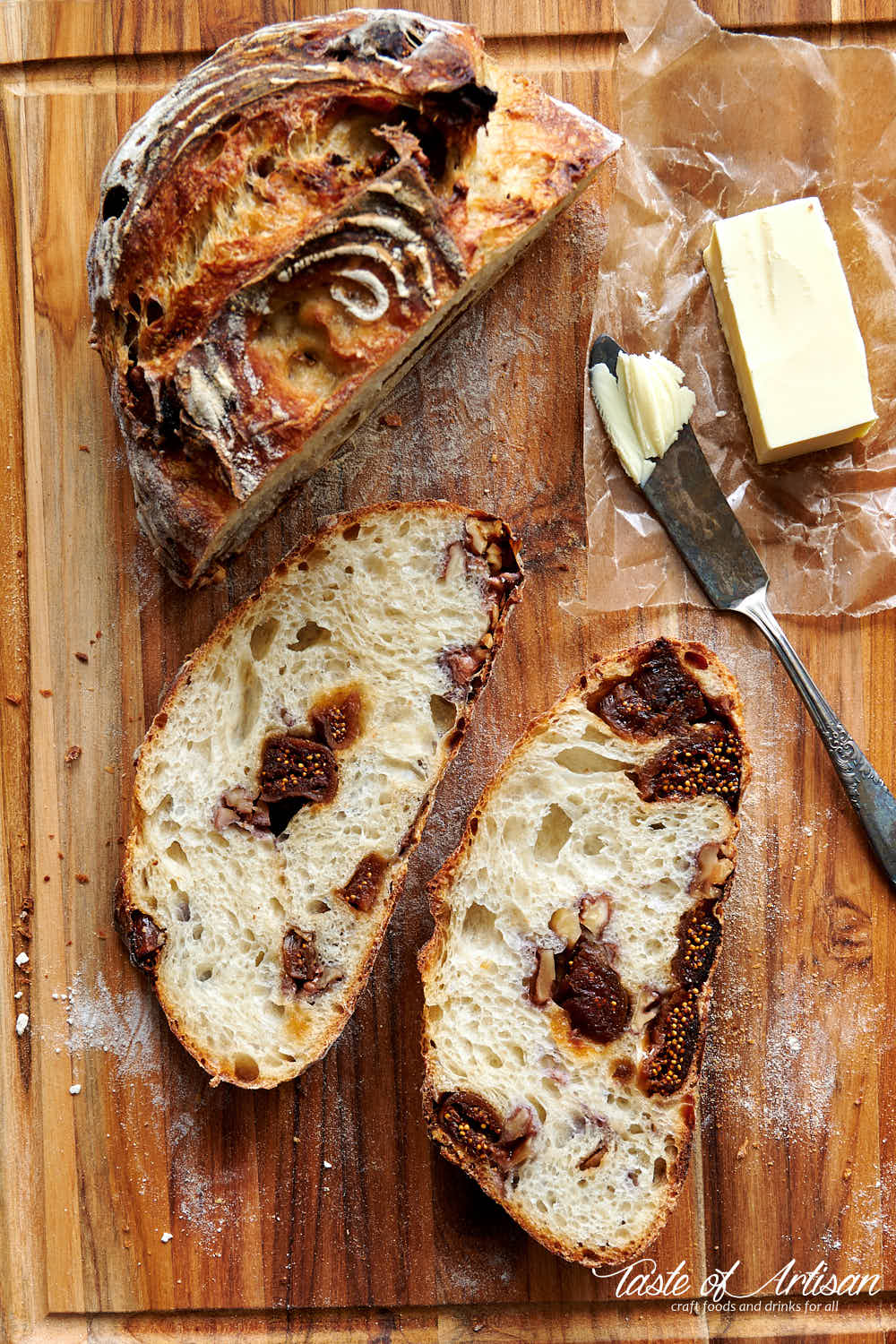 No knead sourdough bread with walnuts and date slices on a cutting board.