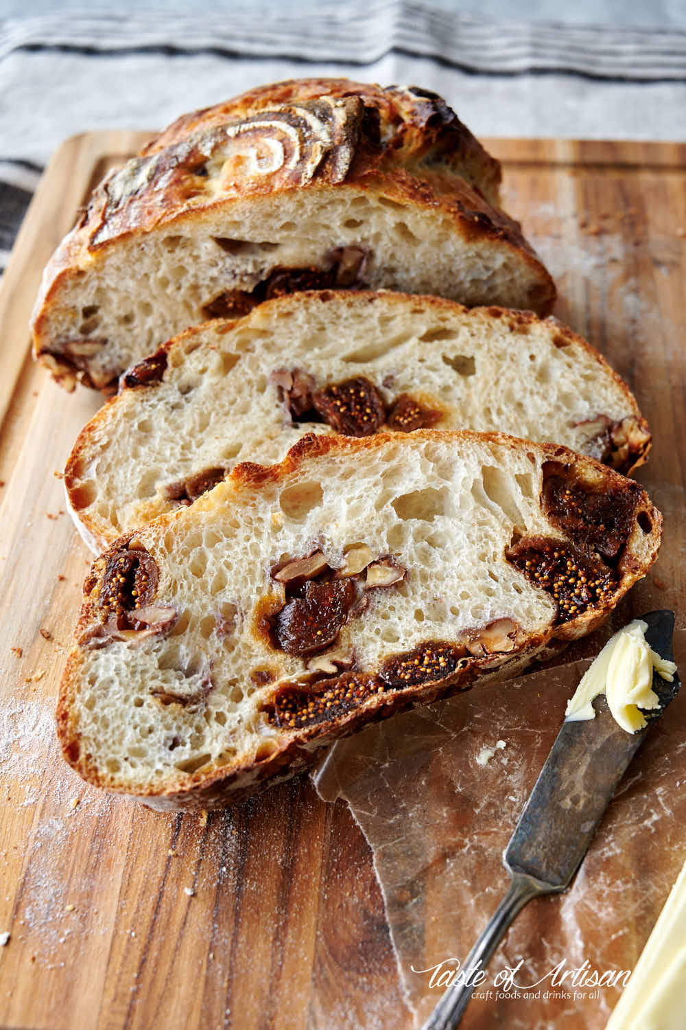 Close u p of slices of sourdough bread with chopped walnuts and quartered dates mixed in.