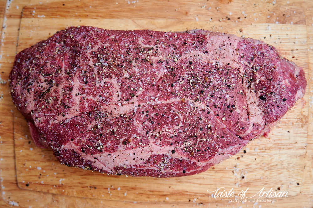 Chuck roast, seasoned with coarse salt and pepper on a wooden board.