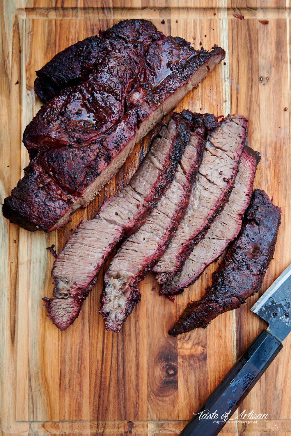 Juicy smoked chuck roast sliced on a cutting board.