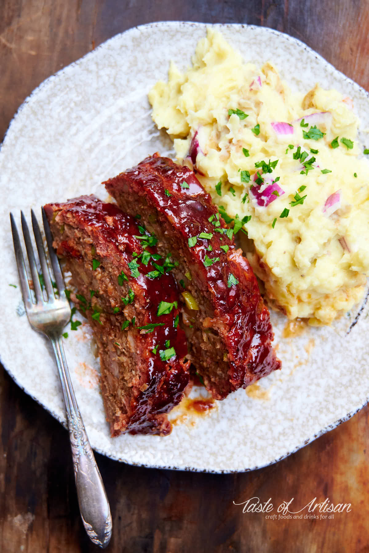 Smoked meatloaf slices on a plate with a fork and mashed potatoes.