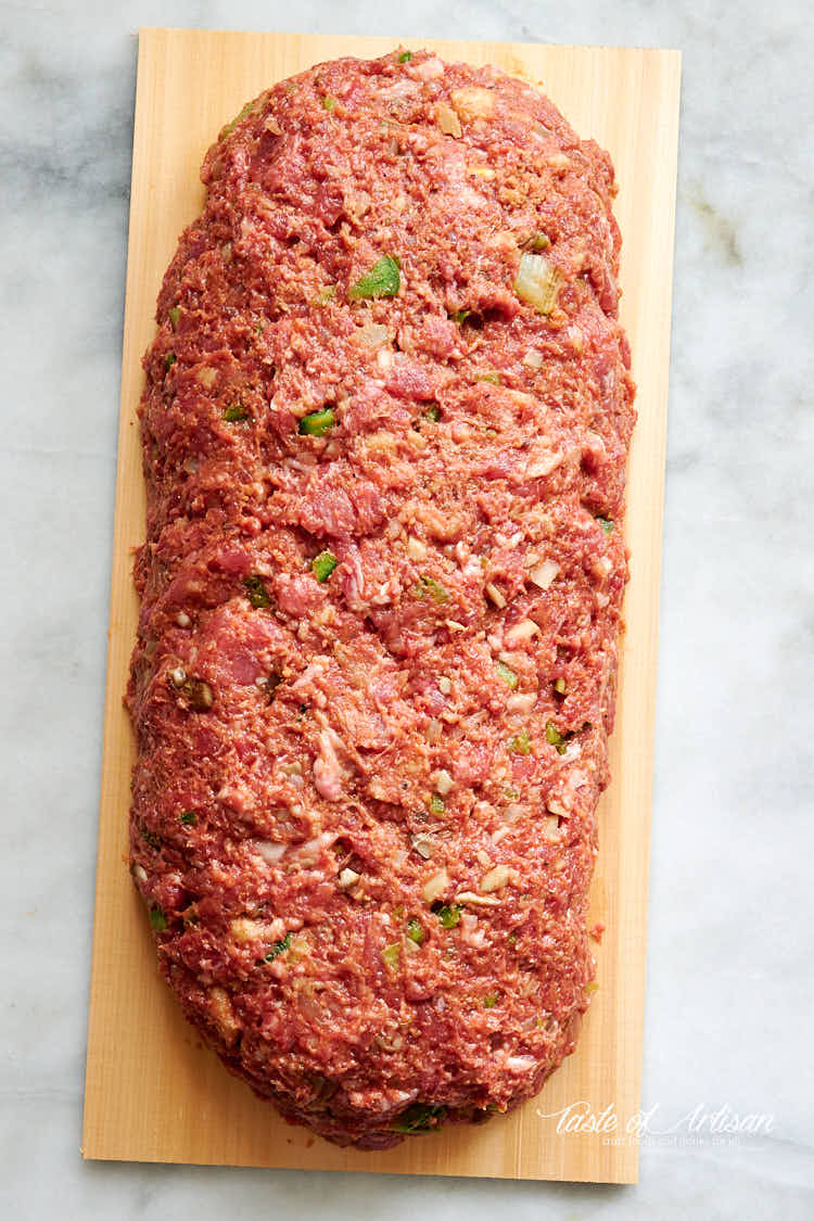 Meatloaf mixture shaped into a log on a cedar plank.