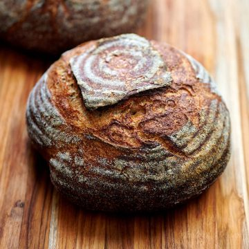 A loaf or rustic sourdough bread on a cutting board.