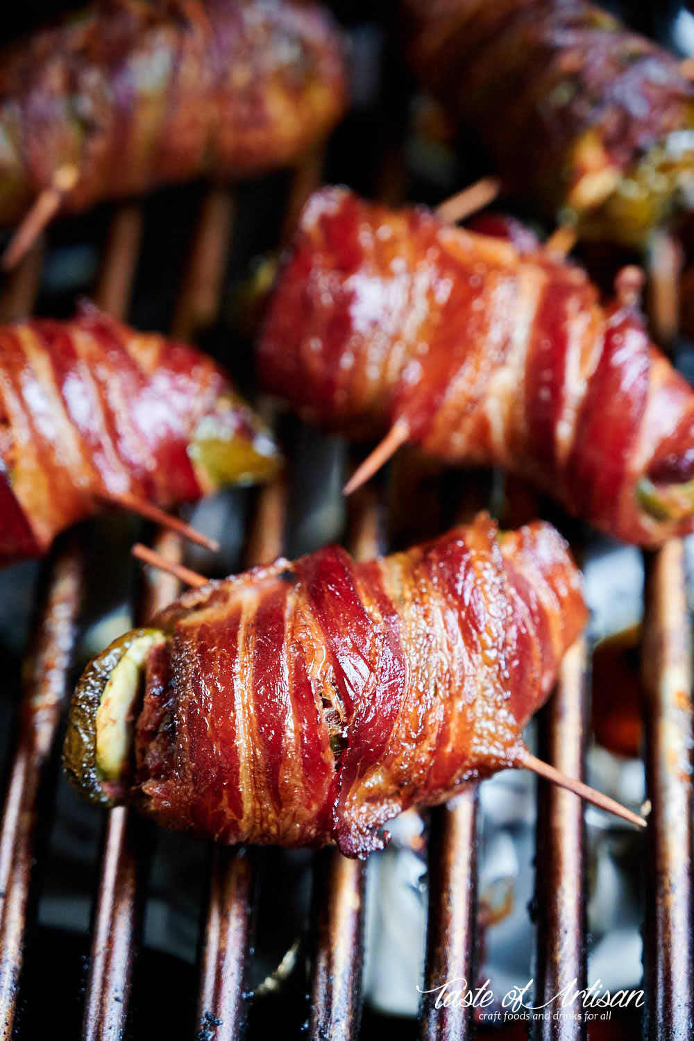 Bacon wrapped jalapeno peppers stuffed with brisket on a grate of a smoker.