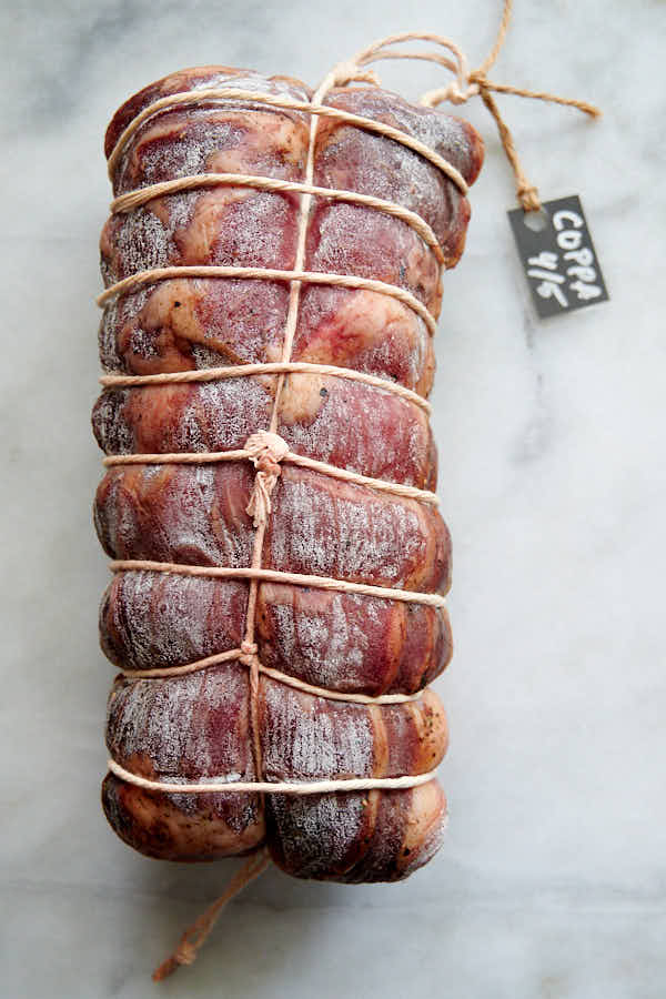 Whole dry cured capicola on a table.