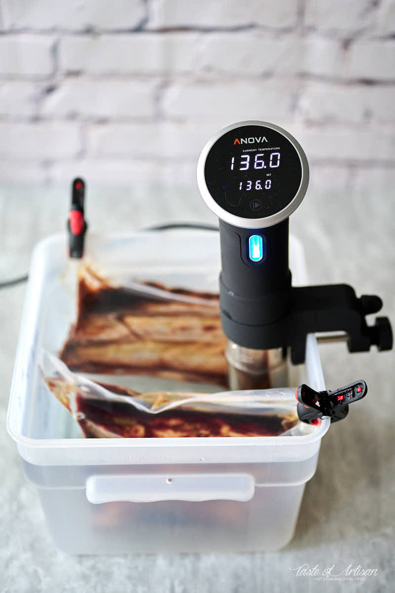 Beef short ribs inside a sous vide bath with sous vide circulator.