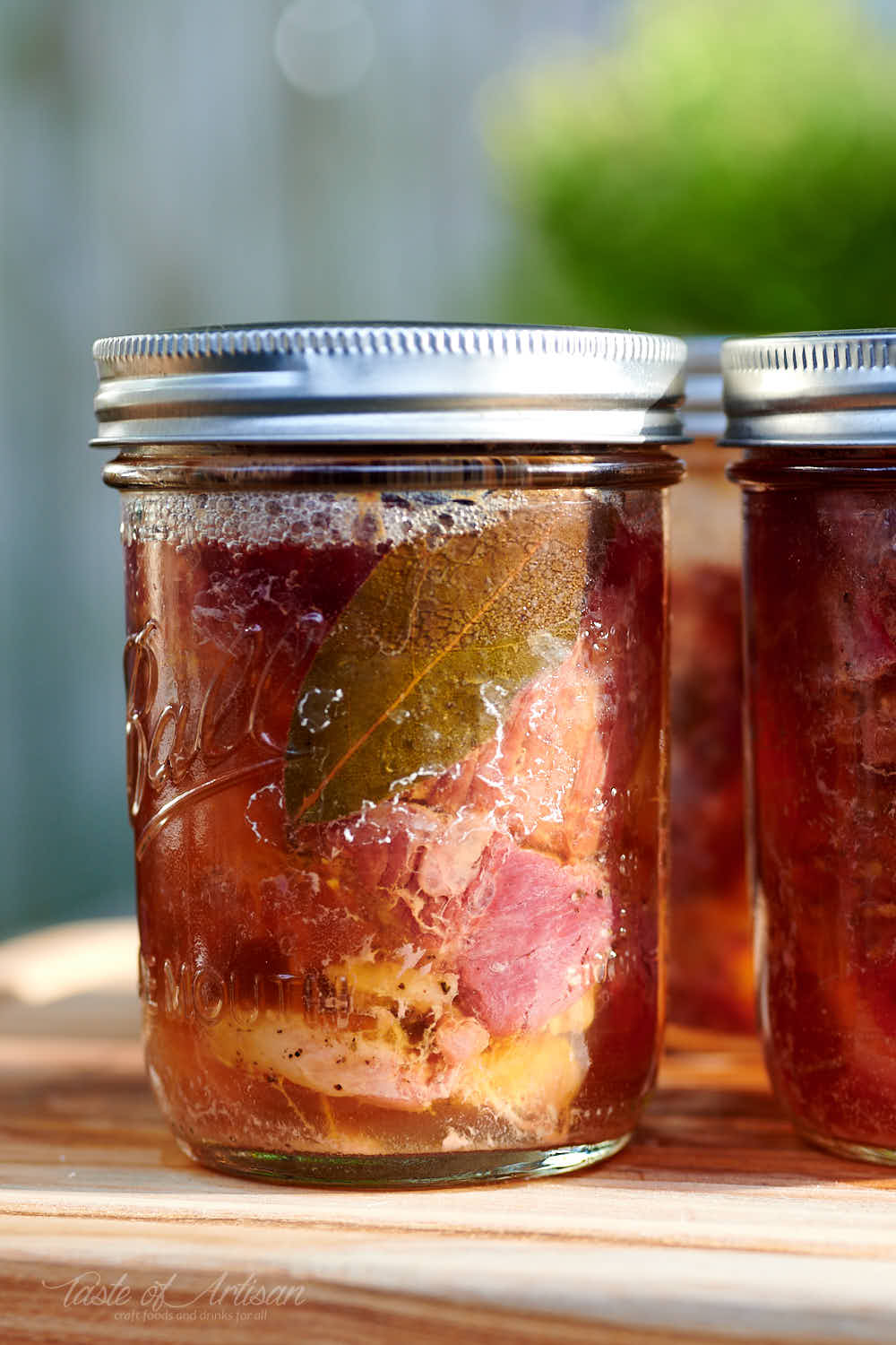 Canned beef in a glass jar with golden juice.
