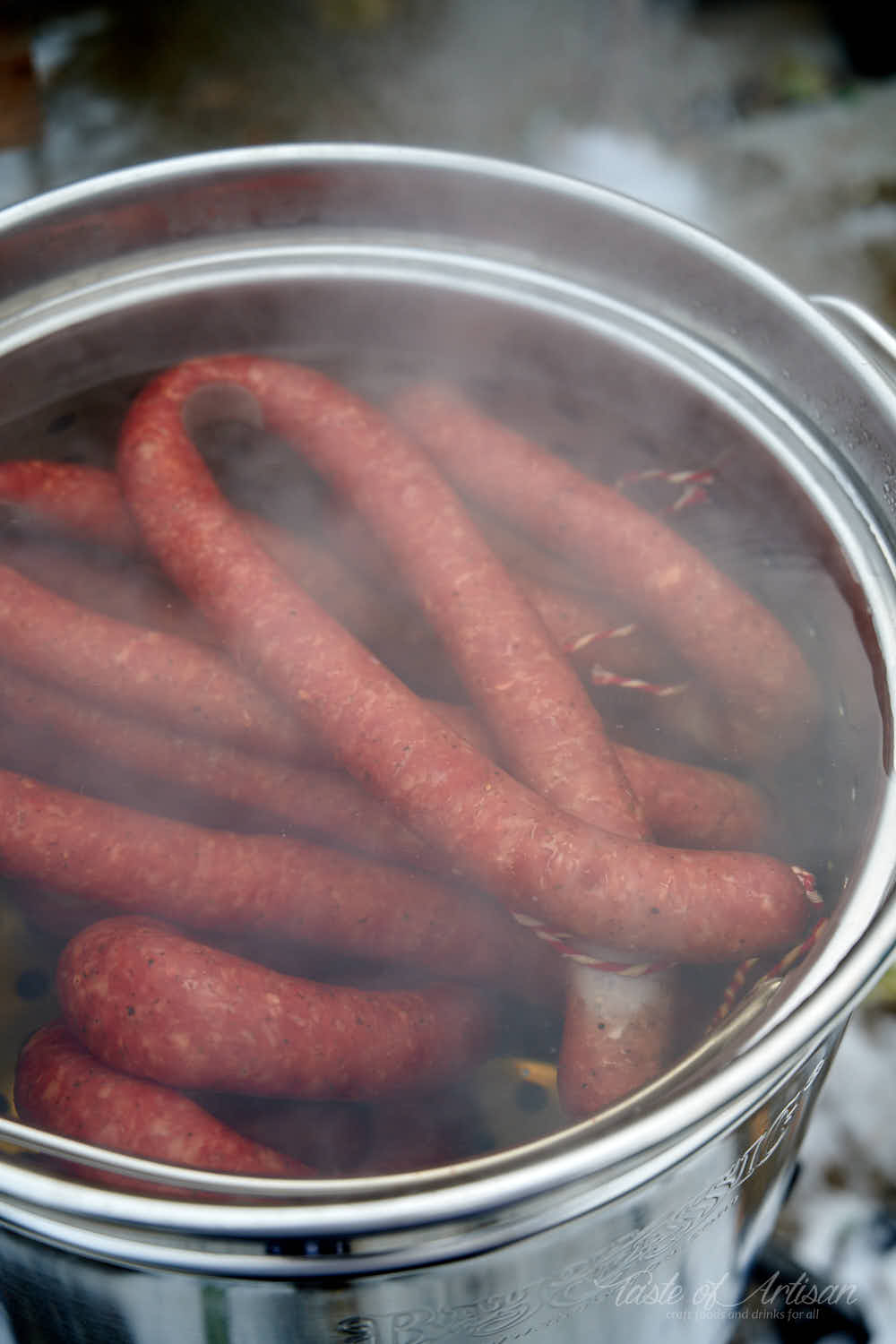 Smoked kielbasa poaching in water.