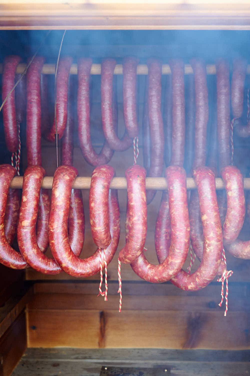 Smoking kielbasa in the smokehouse. Smoke coming out of the open door.