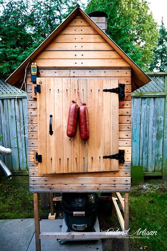 Smoked kielbasa hanging off smokehouse door.
