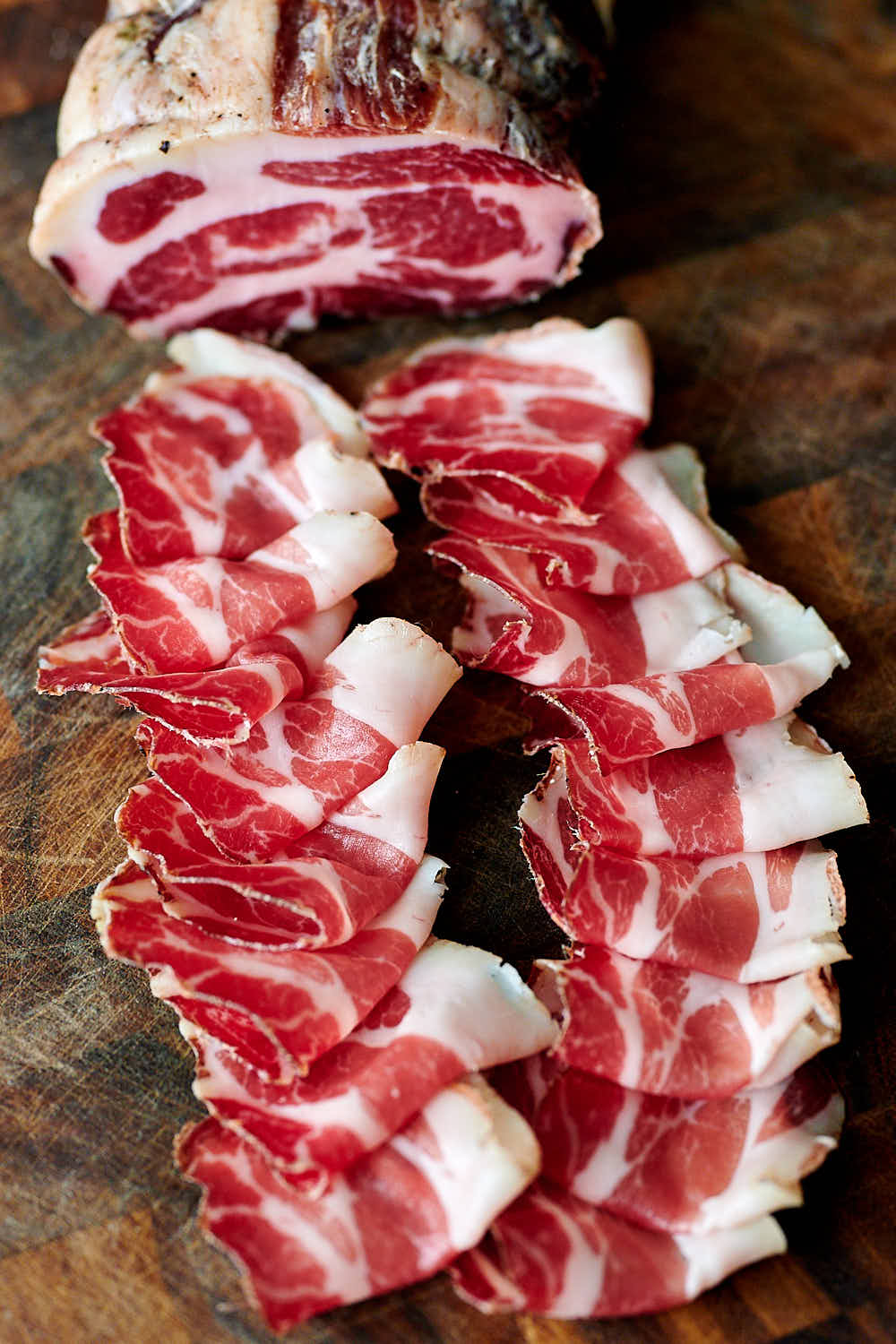 Sliced capicola on a wooden board.