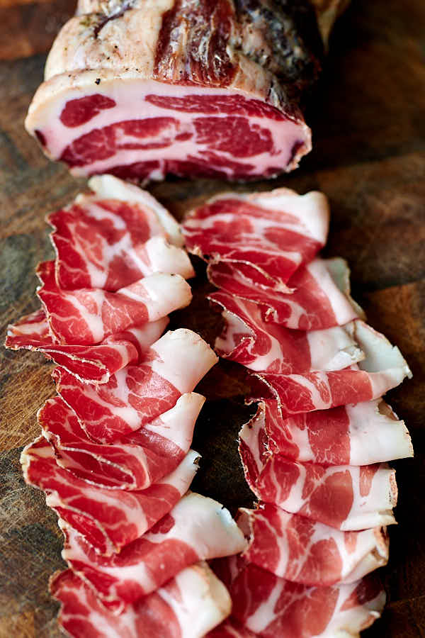 Thinly sliced capicola on a wooden board.