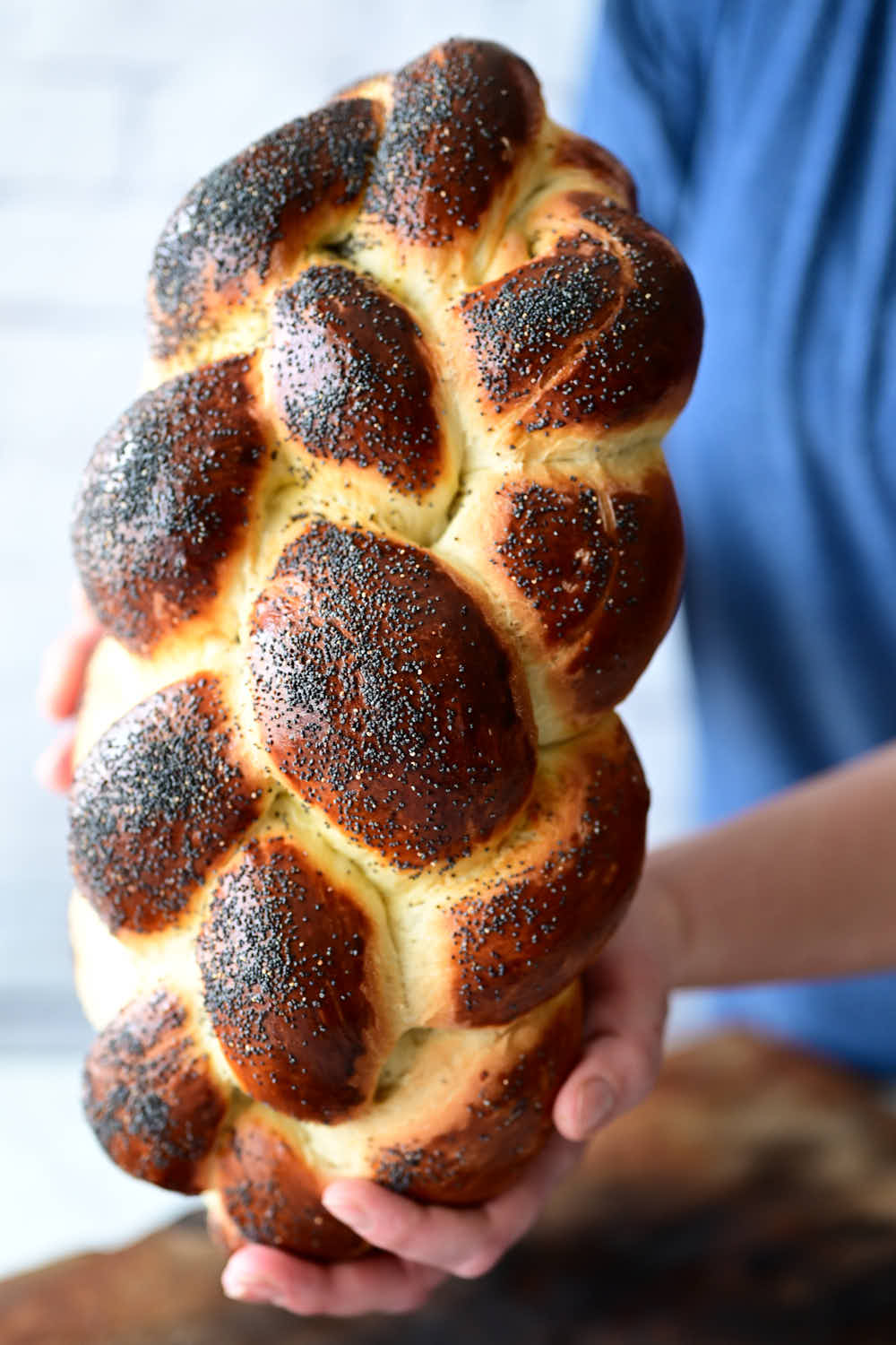 Large challah bread held by hands