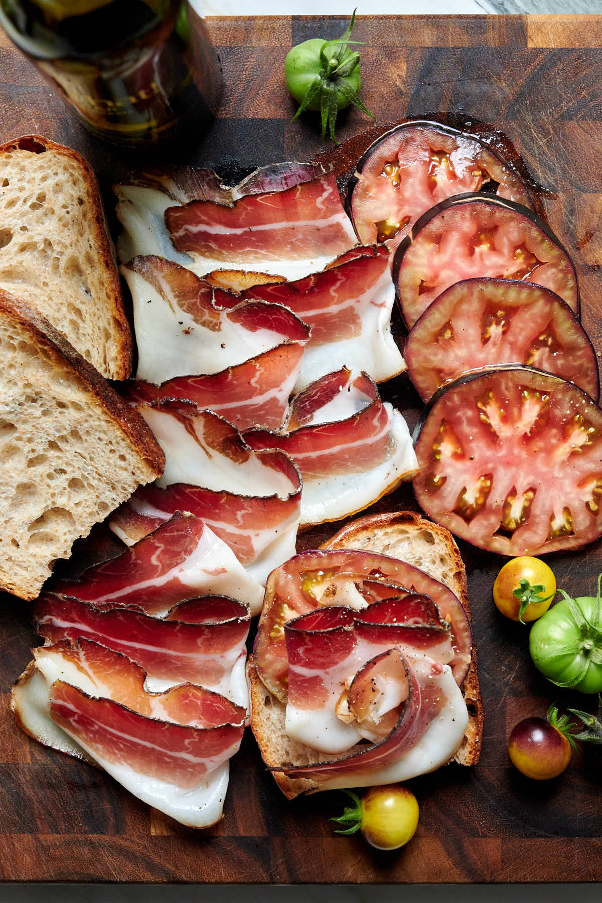Sliced speck served with bread and tomato slices.