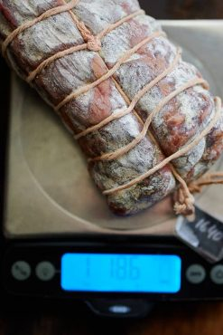 Weighing cured meat on a scale