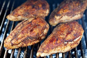 Applying rub to chicken breasts before smoking.