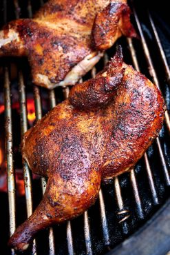 Chicken halves on a smoker grate.