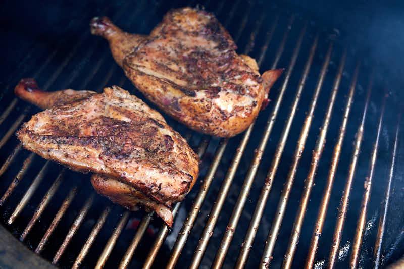 Smoking chicken halves over direct heat skin side down.