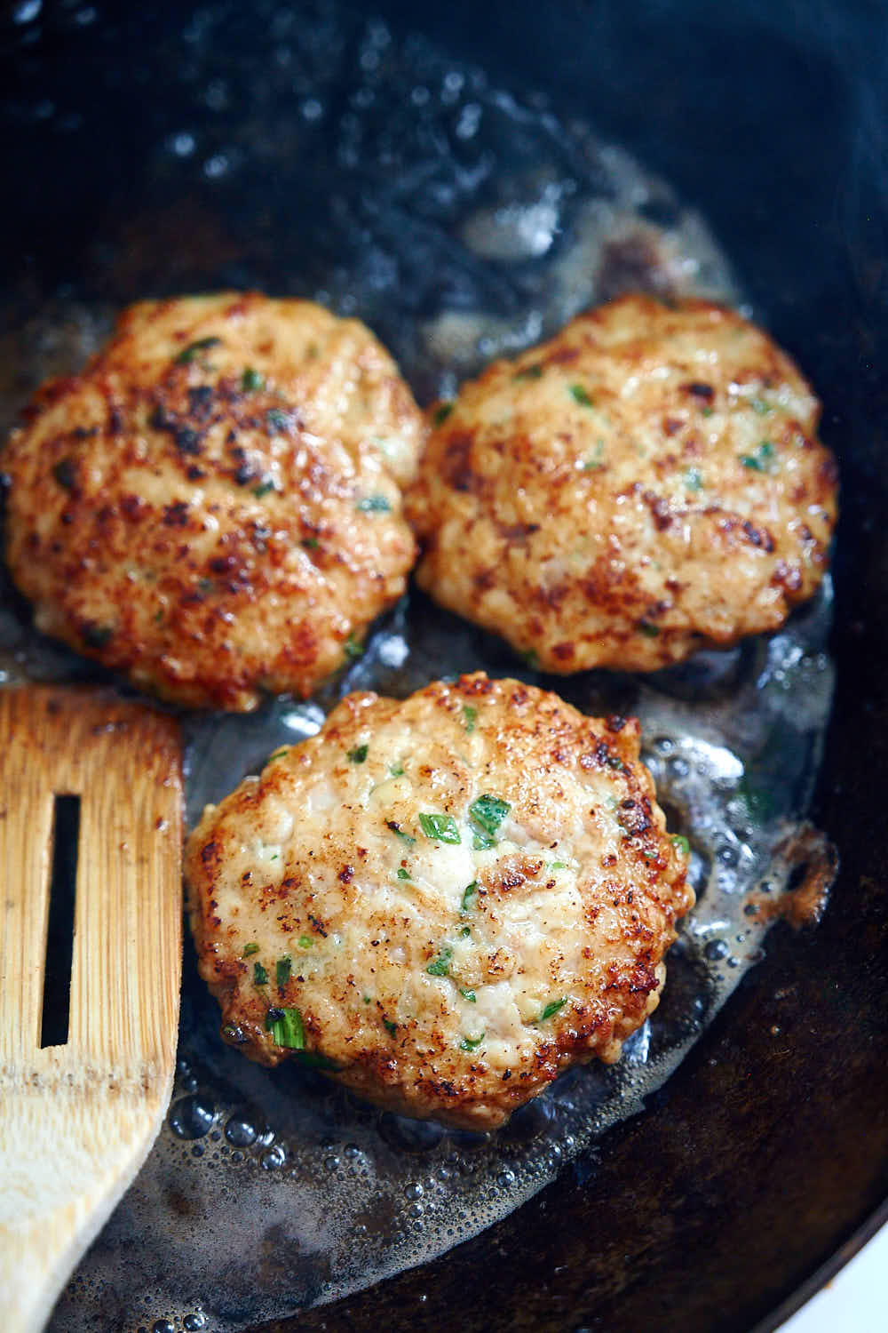 Frying homemade chicken sausage patties on a pan