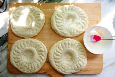 Brush dough with milk for Uzbek bread obi non.