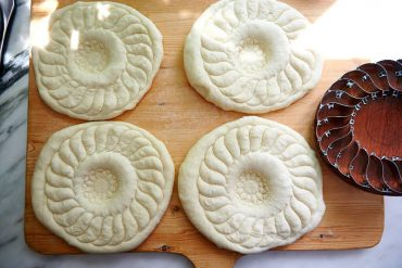 Stamps down center of dough with kechich for Uzbek bread obi non.