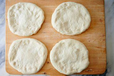 Stretching dough for Uzbek bread obi non.