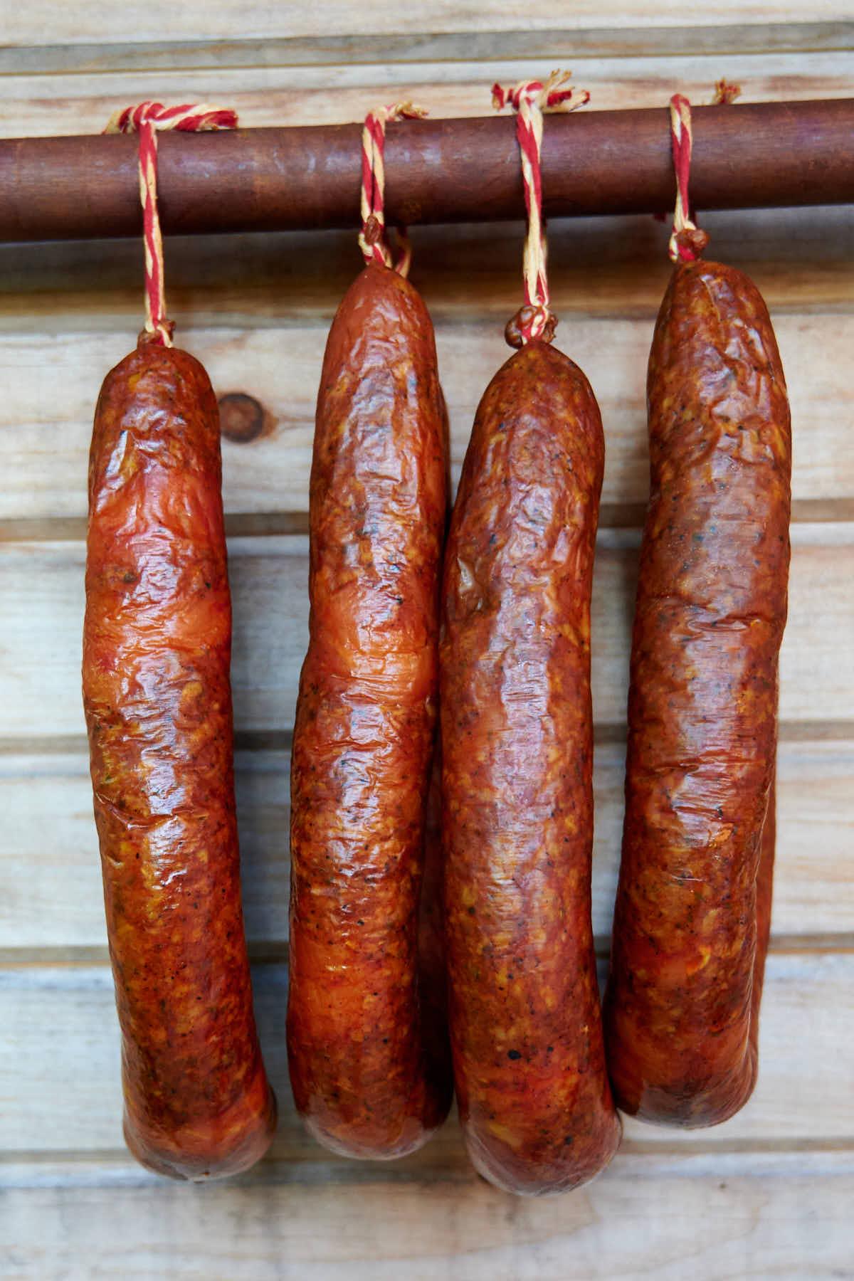 Chicken Andouille Sausage hanging on a smoking stick