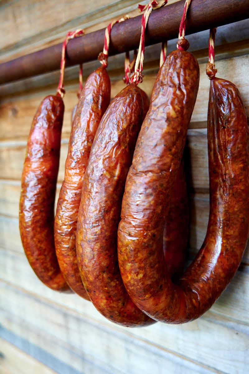 Chicken Andouille Sausage Hanging off Smoking Sticks near Smokehouse