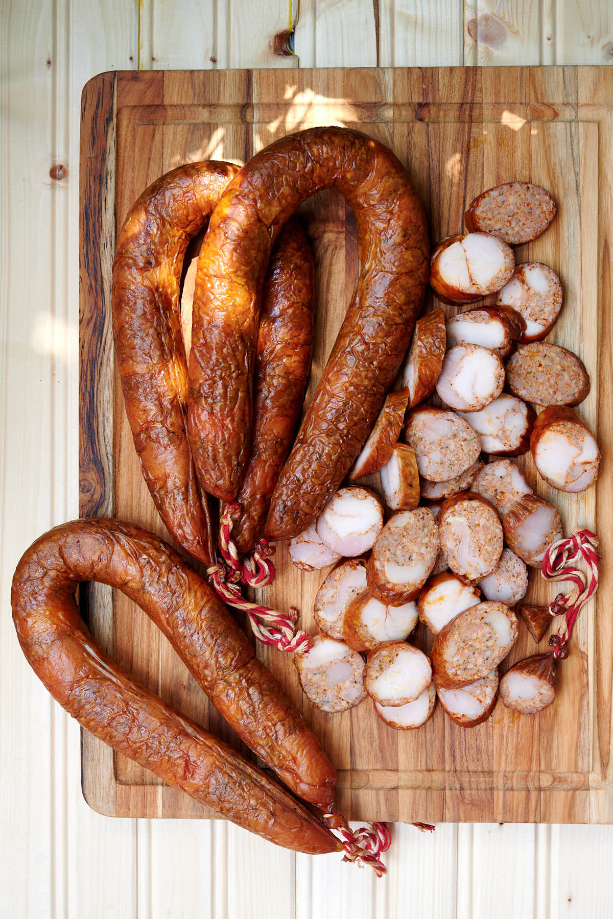 Whole and sliced Homemade Chicken Andouille Sausage on a cutting board