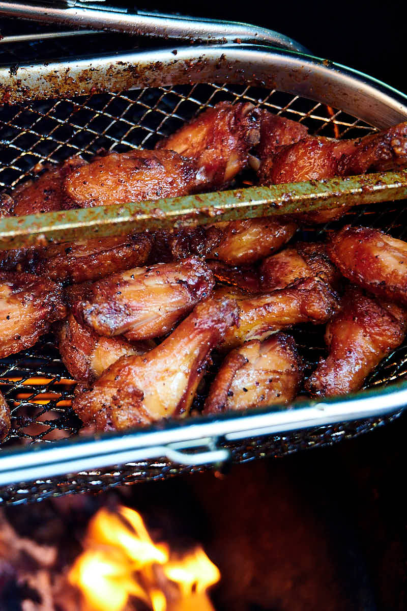 Rotisserie chicken wings in a basket over hot coals.