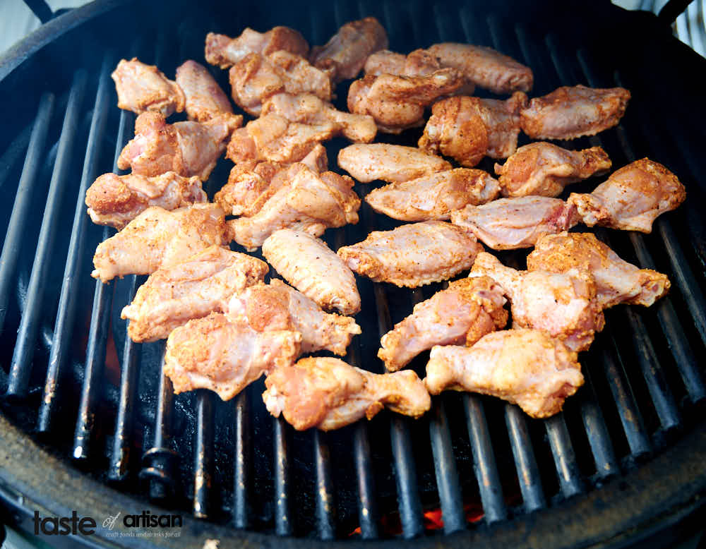Smoking chicken wings over indirect heat at high temperature.