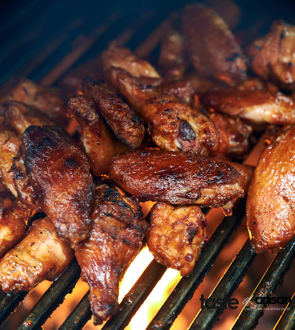 Crisping up smoked chicken wings over direct heat in a two zone smoker setup.