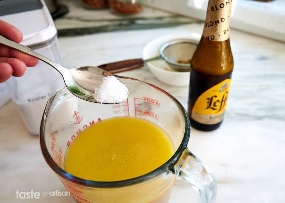 Ingredients for brisket marinade on the table - beer, broth, butter, salt.