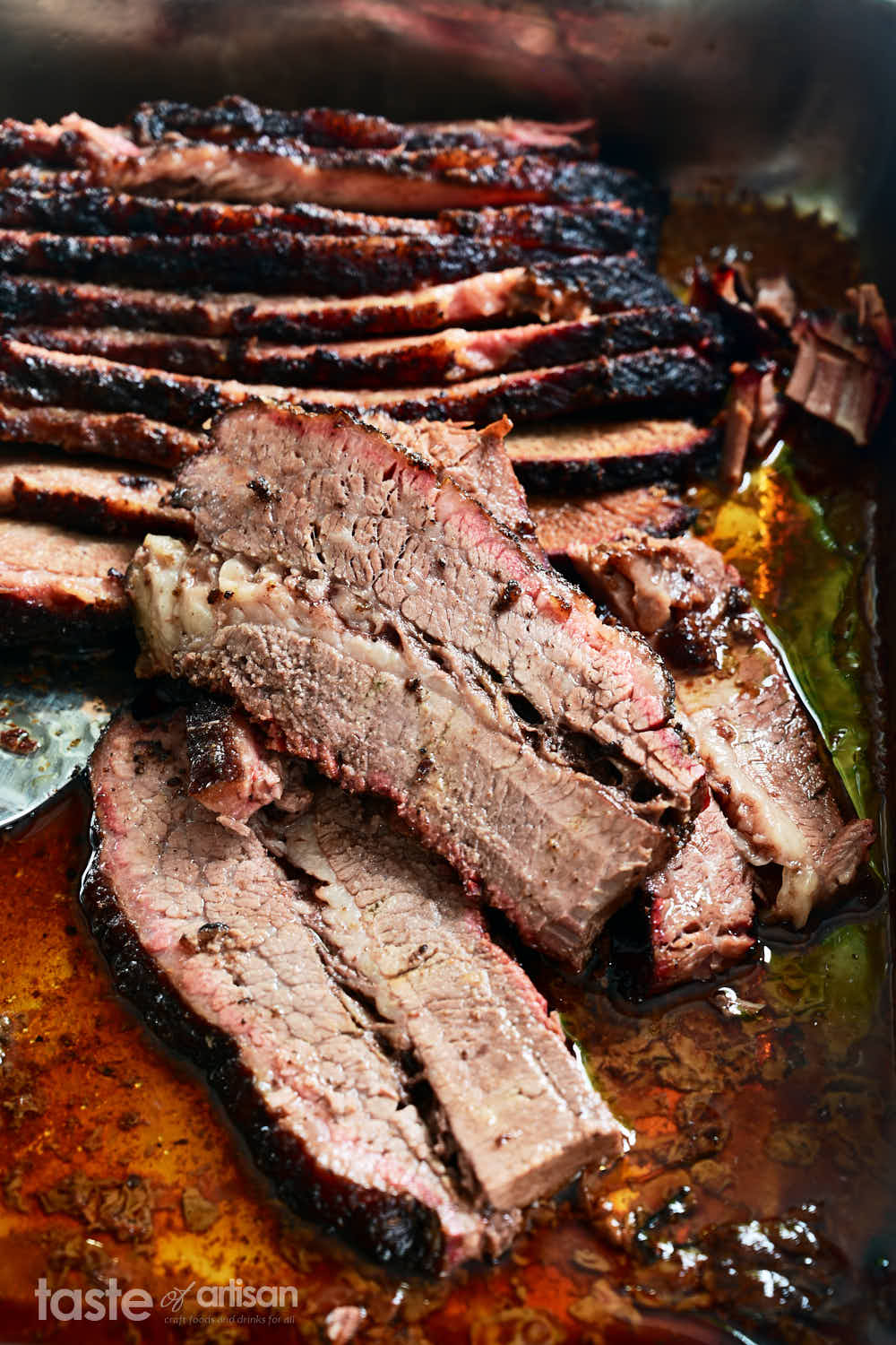 Slices of juicy smoked brisket in a pan.