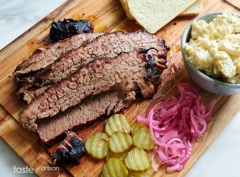 Slices of smoked brisket served with bread, pickles, pickled onions and potato salad.